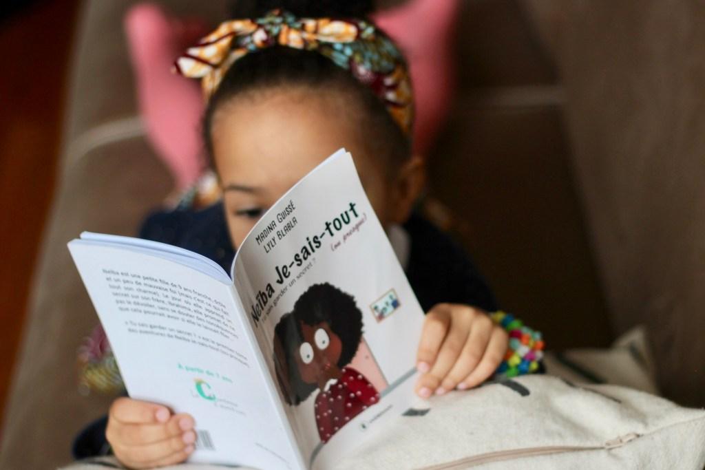 """Une petite fille lisant """"Neïba Je sais tout"""""""